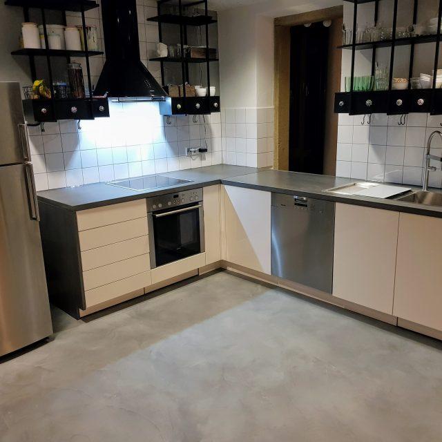 Küchenzeile mit weißen Hochglanzfronten und Beton