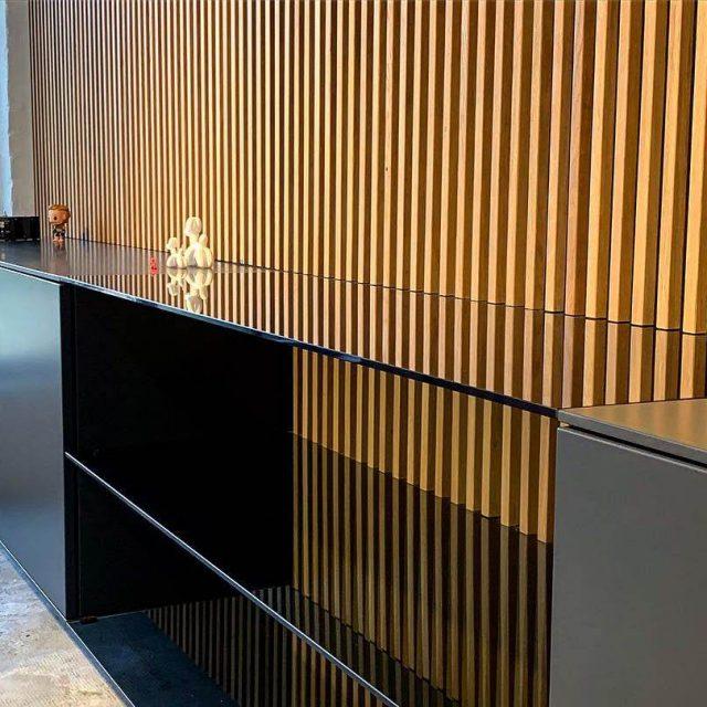 Rückwand aus Eichenleisten und graulackiertes Sideboard mit Rauchglas