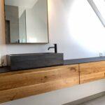 Design-Badezimmer in Eiche, schwarzem Mineralwerkstoff und Vola Armaturen