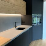 Einbauküche mit Beton, Eiche und schwarz-matten Fronten