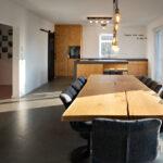 Wohnraum mit maßgeschneiderter Familienküche, Esstisch und Schiebetür